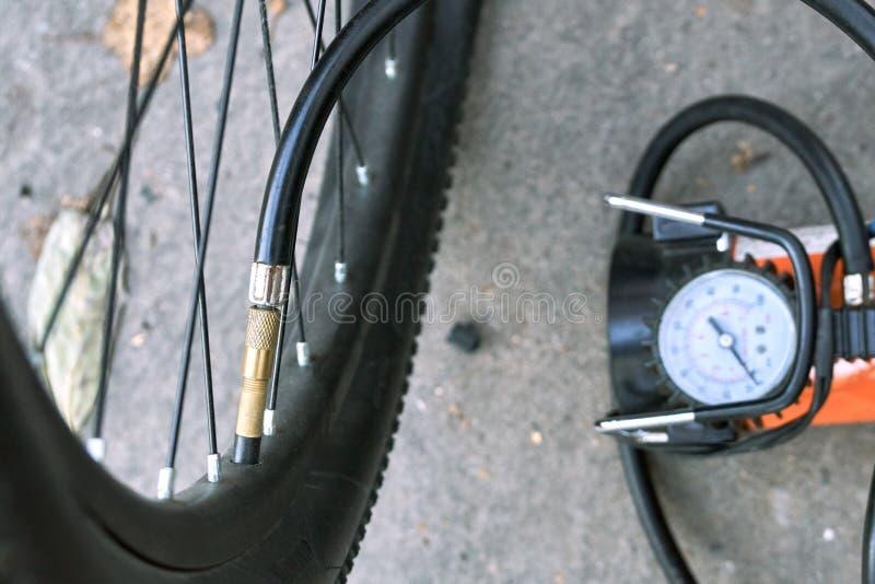 Pompando su una gomma della bicicletta facendo uso di un compressore elettrico dell'automobile dell'aria fotografia stock libera da diritti
