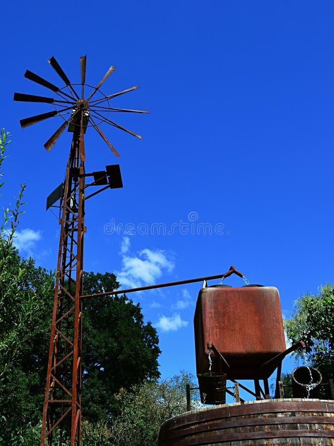Pompe à eau actionnée par le vent avec les tuyaux rouillés, les réservoirs d'eau carrés rouillés et deux seaux en bois comme syst photos libres de droits