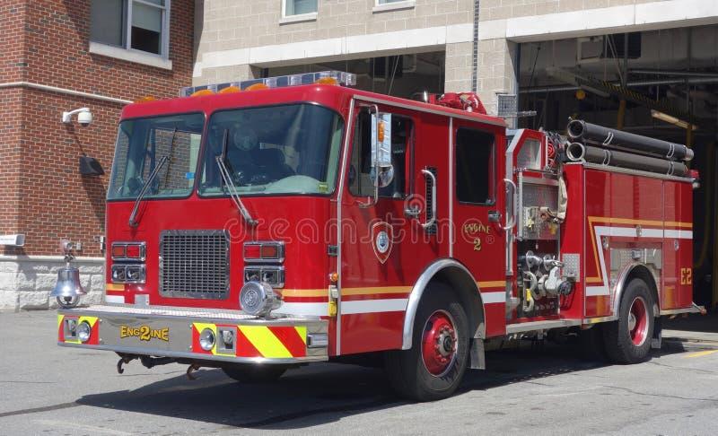 Pompe à incendie rouge se déplaçant hors de la caserne de pompiers photos stock