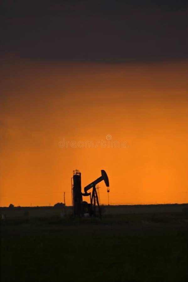Pompe de pétrole au coucher du soleil image libre de droits