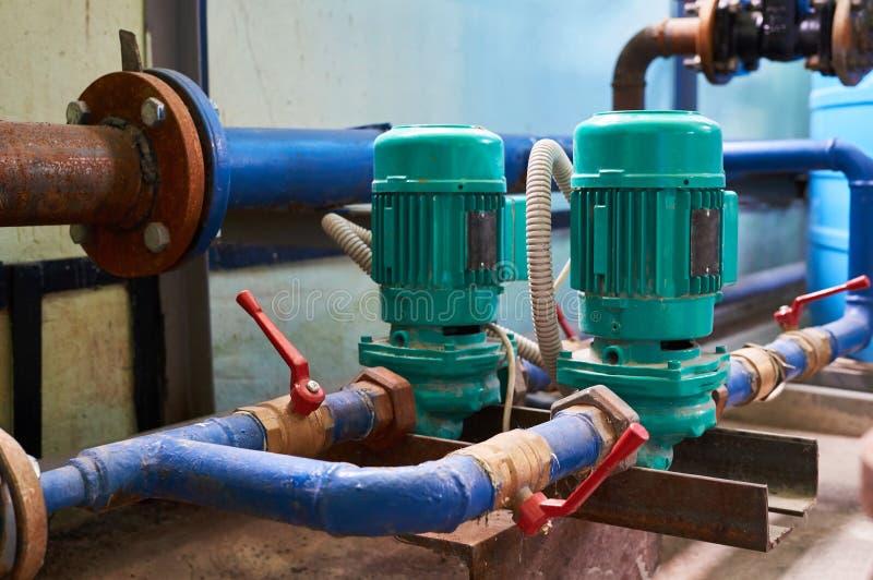 Pompe deux électrique verte sur une canalisation de l'eau peinte dans le bleu Fond industriel image stock