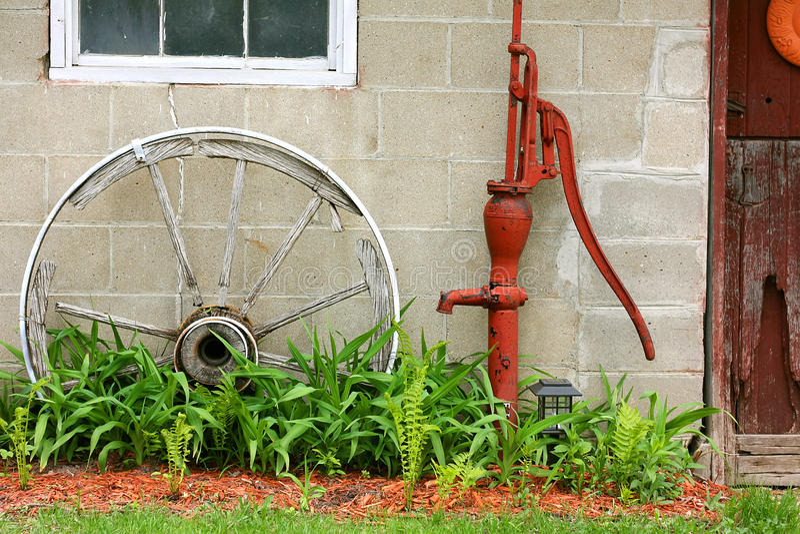 Pompe en bois antique à roues et à eau par la grange image stock