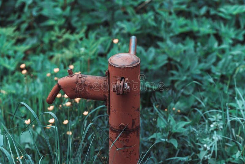Pompe ? main rouill?e de fontaine d'eau de cru dans le village russe T?te de puits abandonn?e de l'eau photos stock