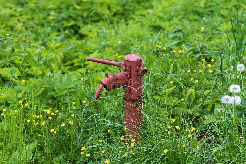 Pompe ? main rouill?e de fontaine d'eau de cru dans le village russe T?te de puits abandonn?e de l'eau photo libre de droits