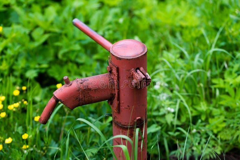 Pompe ? main rouill?e de fontaine d'eau de cru dans le village russe T?te de puits abandonn?e de l'eau photos libres de droits