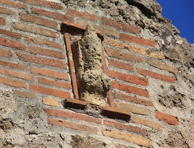 Pompeii Brothel. A stone phallus attached to the facade of a ruined home in Pompeii indicates that the home was once a brothel royalty free stock photo