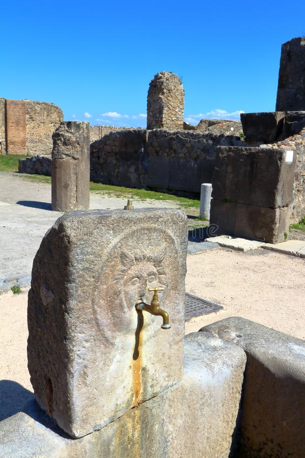 Pompeii, Italy: Fountain. Pompeii, Italy - March 28, 2017: Ruins at Pompeii archaeological site, the ancient Roman city, destroyed in 79 BC by the eruption of stock image