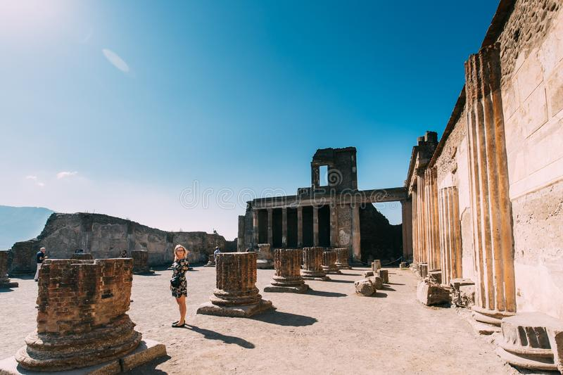Pompeii, Italy. Young Woman Tourist Looking At Ancient Columns In Sunny Day royalty free stock photos
