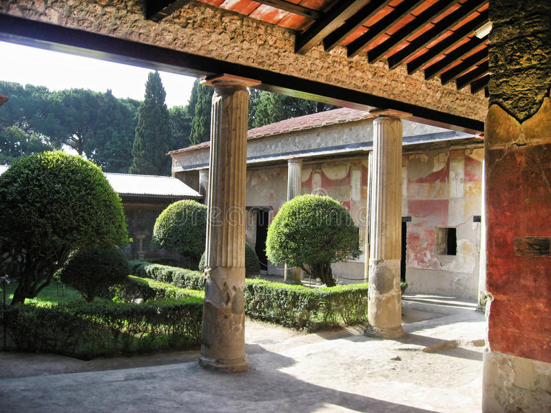 Pompeii Roman House. The ruins of a Pompeii roman house with columns and a garden. The walls have red stucco. Campania, south of Italy royalty free stock image