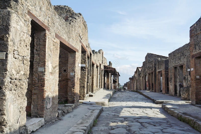 Pompeii Roman Ruins Stone Street. The roman ruins of Pompeii, a stone street with the walls and doors of the ancient houses and businesses. South of Italy royalty free stock images
