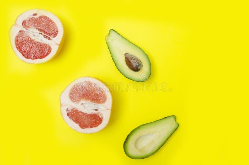 Pompelmo ed avocado affettati su backgroun giallo luminoso, vista superiore fotografie stock libere da diritti