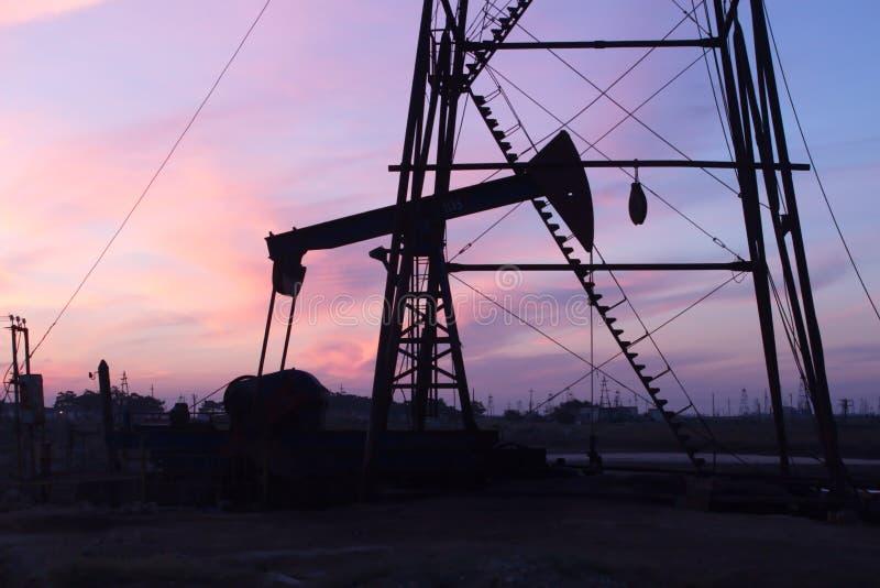 Pompes à huile et coucher du soleil photo stock