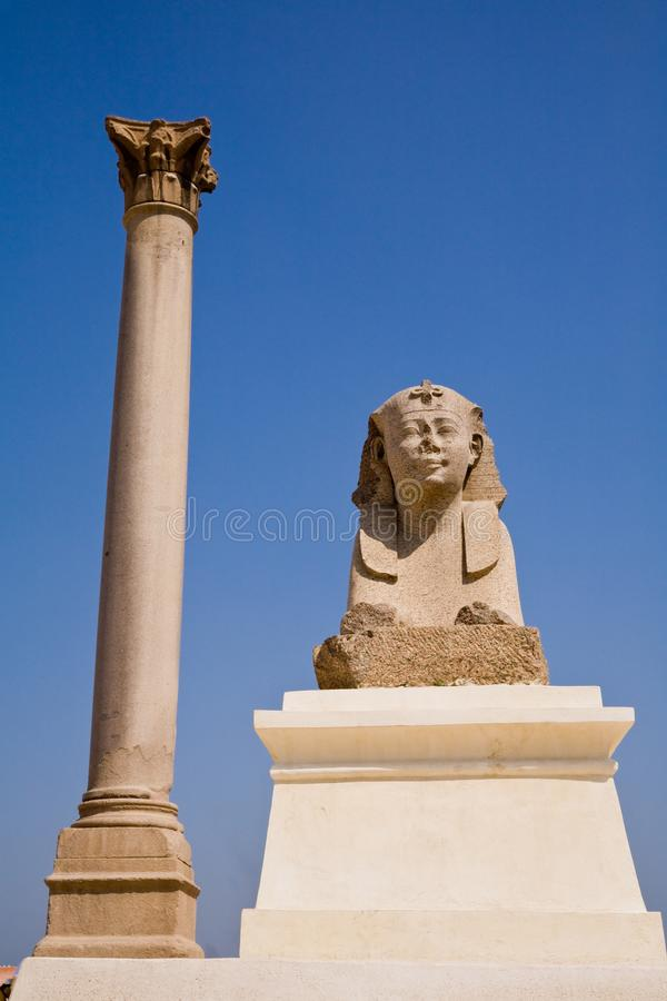 Pompey`s Pillar and sphinx in Alexandria, Egypt. Pompey`s Pillar and a sphinx in Alexandria, Egypt royalty free stock image