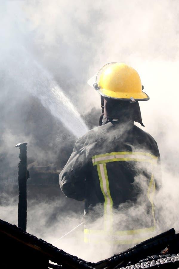 Pompier éteignant un incendie de Chambre image libre de droits