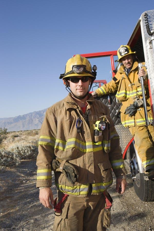 Pompier avec le collègue se tenant à la porte des sapeurs-pompiers photos stock