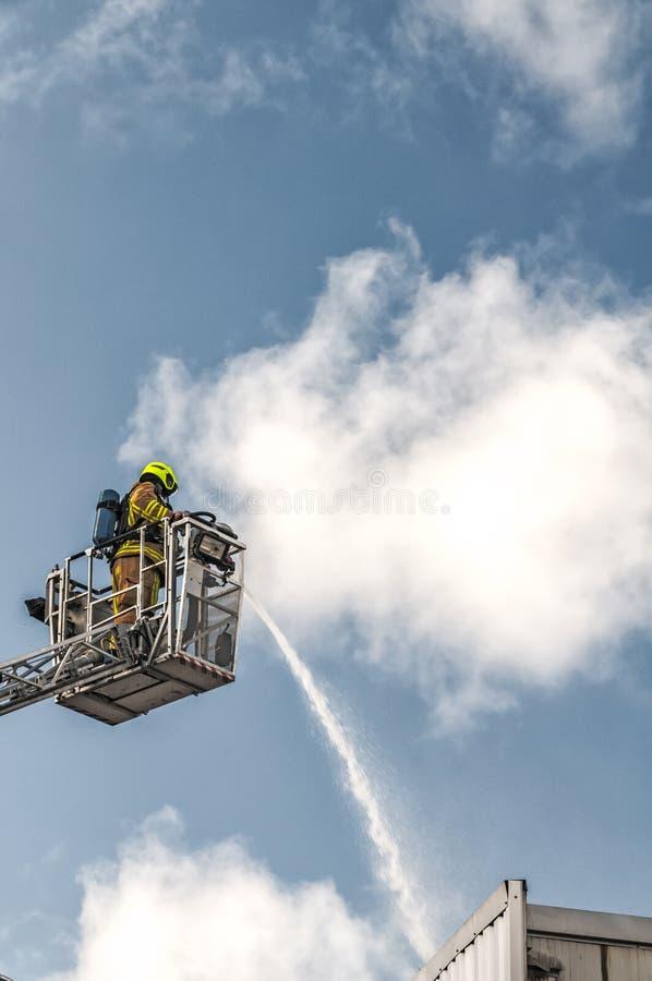 Pompier avec le tuyau d'extincteur photos stock