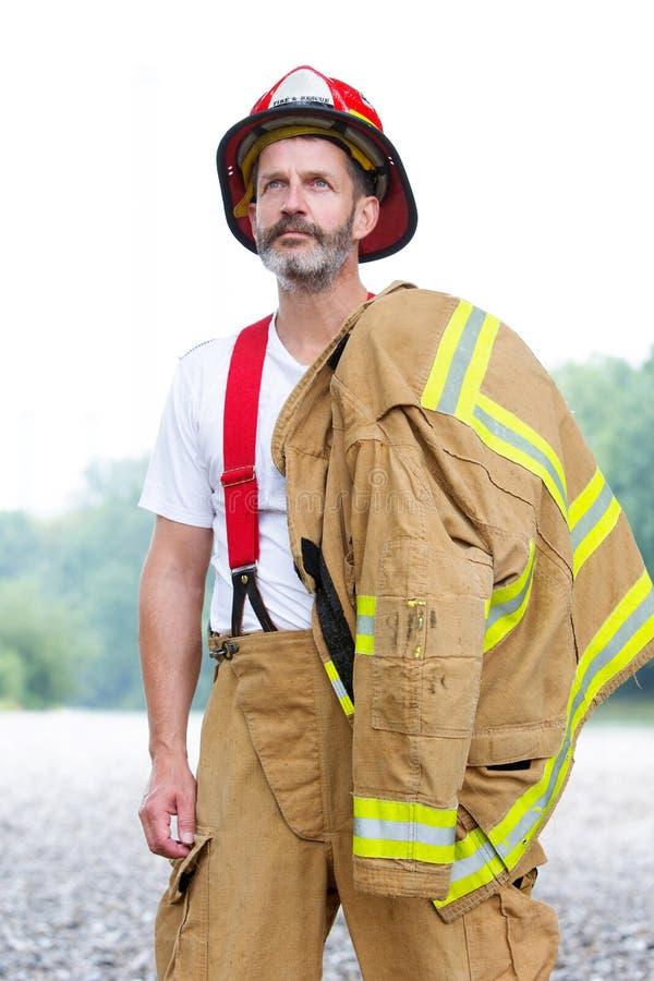 Pompier beau dans l'uniforme se tenant dehors photo stock