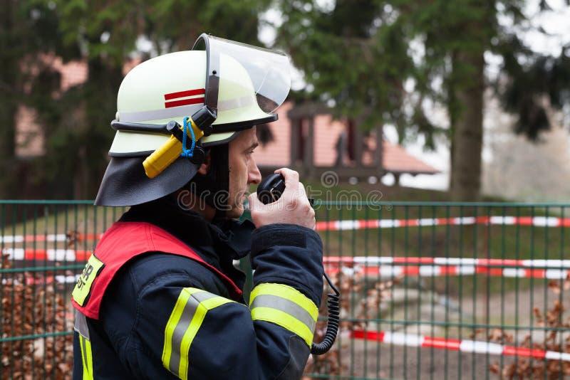 Pompier dans l'action et étincelle avec le poste radio photo stock