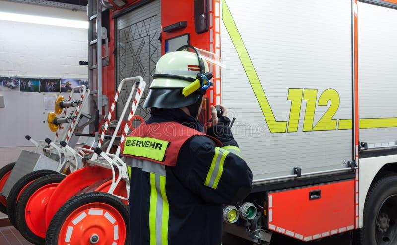 Pompier dans une étincelle de camion de pompiers de corps de sapeurs-pompiers avec le poste radio images libres de droits