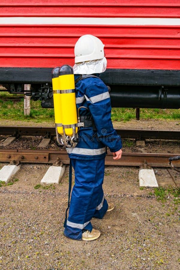 Pompier portant la position uniforme protectrice à côté d'un train du feu photographie stock