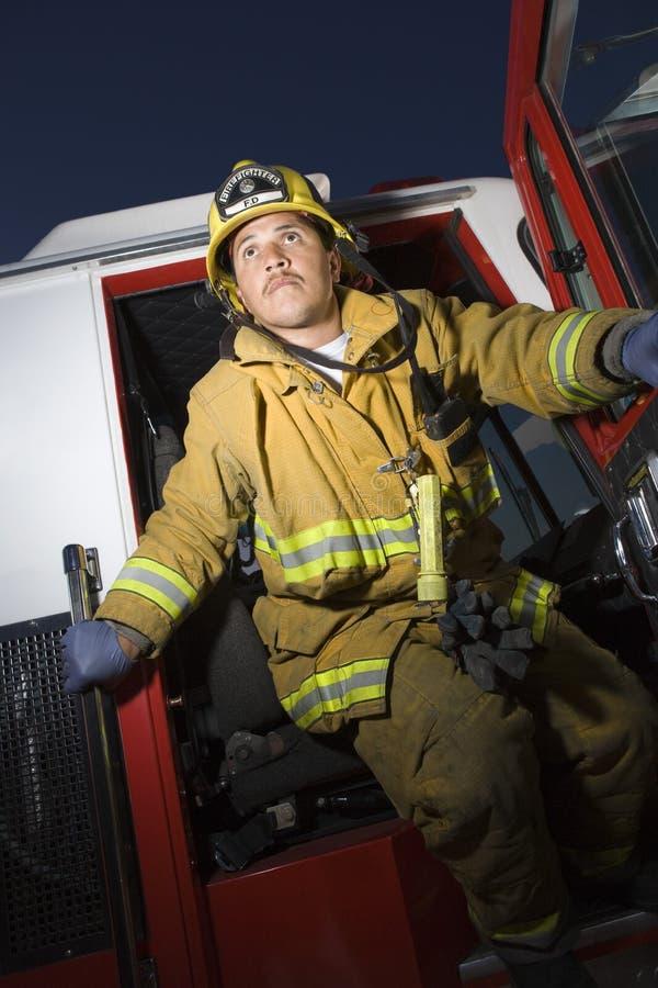 Pompier se tenant à la porte des sapeurs-pompiers image stock