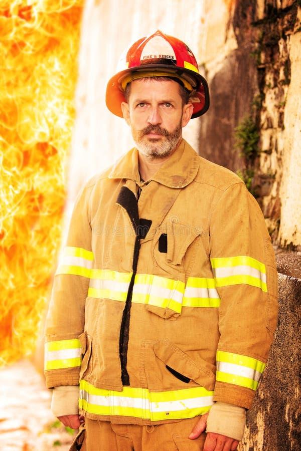 Pompier se tenant devant le mur du feu image libre de droits