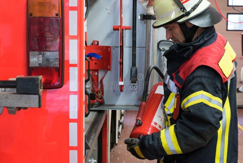 Pompier sur le camion de pompiers avec un extincteur image libre de droits