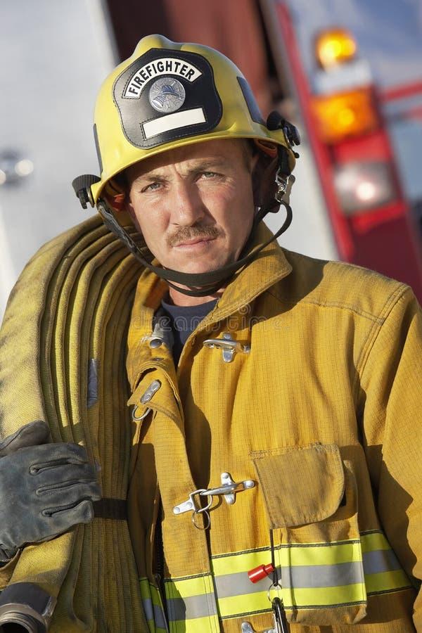 Pompier tenant le tuyau sur l'épaule photo stock