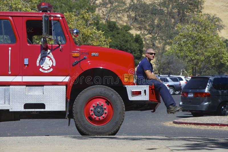 Pompiere americano che si siede sul paraurti di un camion dei vigili del fuoco immagini stock