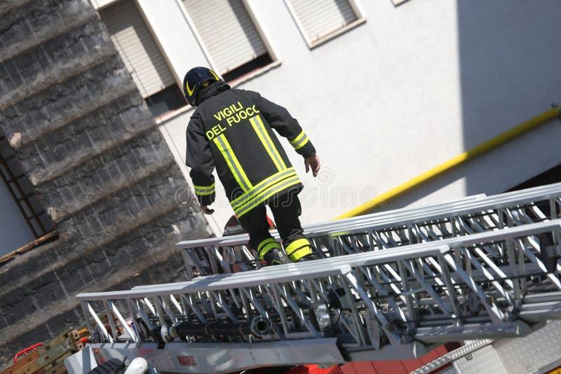 Pompiere che cammina sulla scala estesa dei firetrucks durante fotografia stock