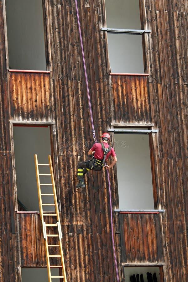 Pompiere che scala durante l'ascesa che si cala in corda doppia da una costruzione fotografia stock libera da diritti