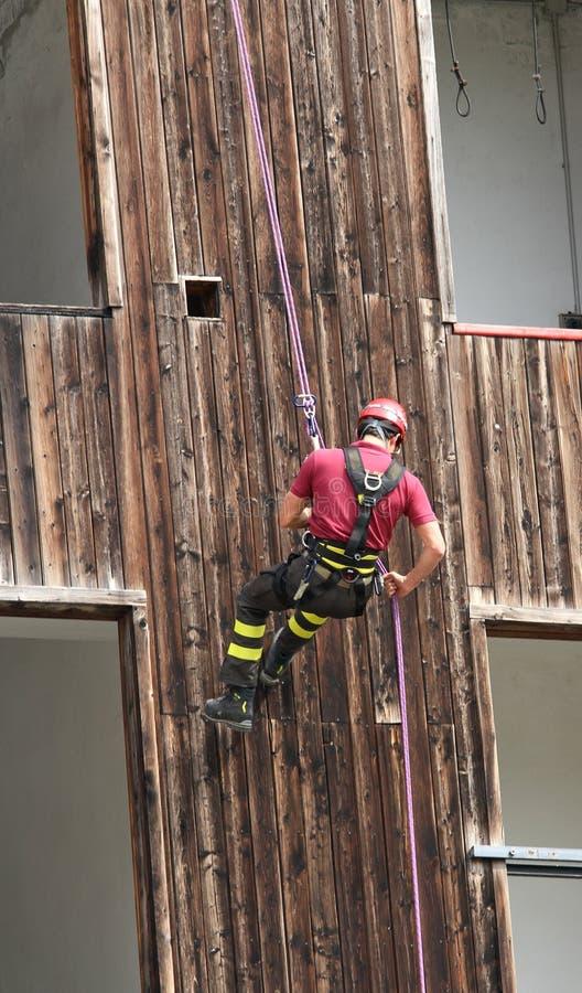 Pompiere che scala durante l'ascesa che si cala in corda doppia da una costruzione immagine stock