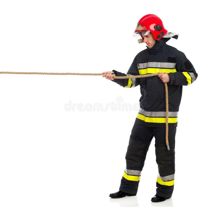 Pompiere che tira una corda immagine stock