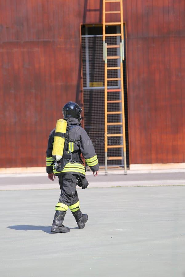 Pompiere con il cilindro di ossigeno fotografia stock libera da diritti