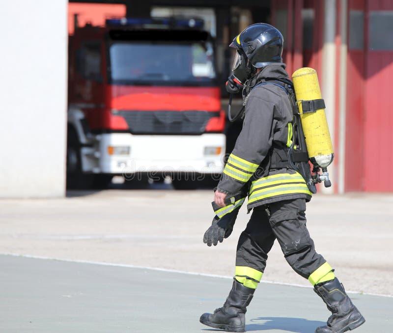 Pompiere con il grande cilindro di ossigeno ed il respiratore automatico fotografia stock