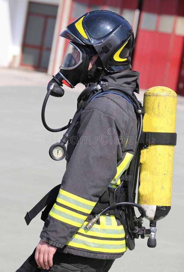 Pompiere con il grande cilindro di ossigeno giallo ed i hel protettivi fotografie stock libere da diritti