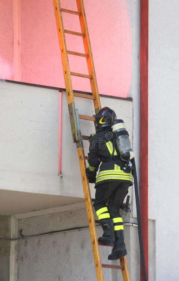 Pompiere con il legno del cilindro di ossigeno che sale una scala fotografia stock