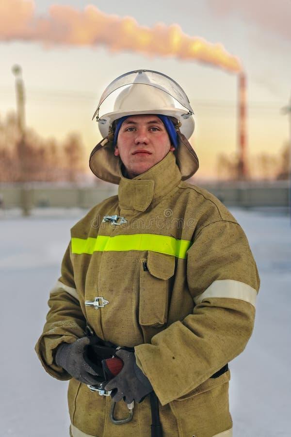 Pompiere di Portert Un uomo bianco in camici ed in un casco sta stando all'aperto nell'inverno e sta esaminando direttamente la m fotografia stock libera da diritti