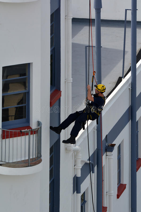 Pompiere durante calarsi in corda doppia esercizio fotografia stock libera da diritti