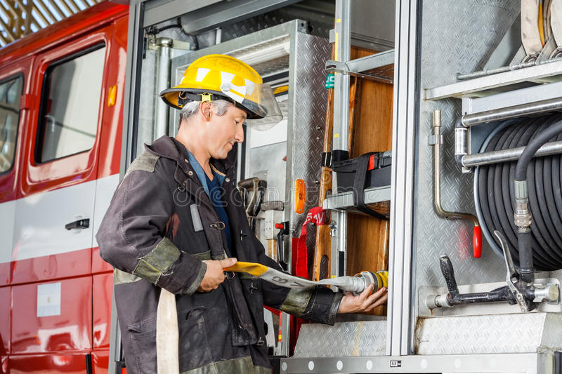 Pompiere Fixing Water Hose in camion a fuoco fotografie stock