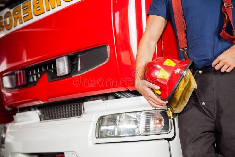 Pompiere Holding Red Helmet mentre appoggiandosi immagine stock libera da diritti
