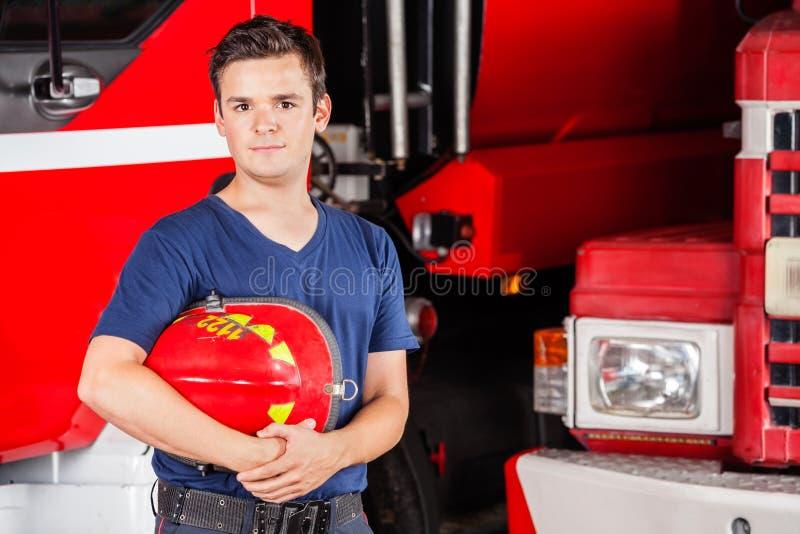Pompiere maschio sicuro Holding Red Helmet fotografia stock libera da diritti
