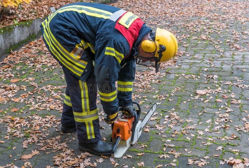 Pompiere nell'azione con la motosega fotografia stock libera da diritti
