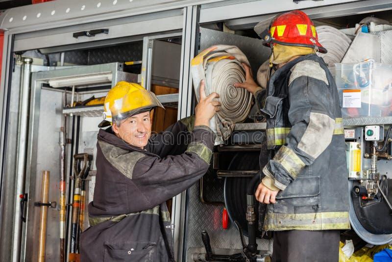 Pompiere sorridente Assisting Colleague In che rimuove tubo flessibile immagini stock libere da diritti