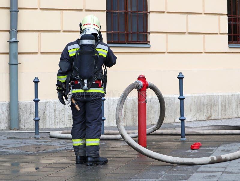 Pompiere sul lavoro con il carro armato di ossigeno e del tubo flessibile fotografie stock libere da diritti