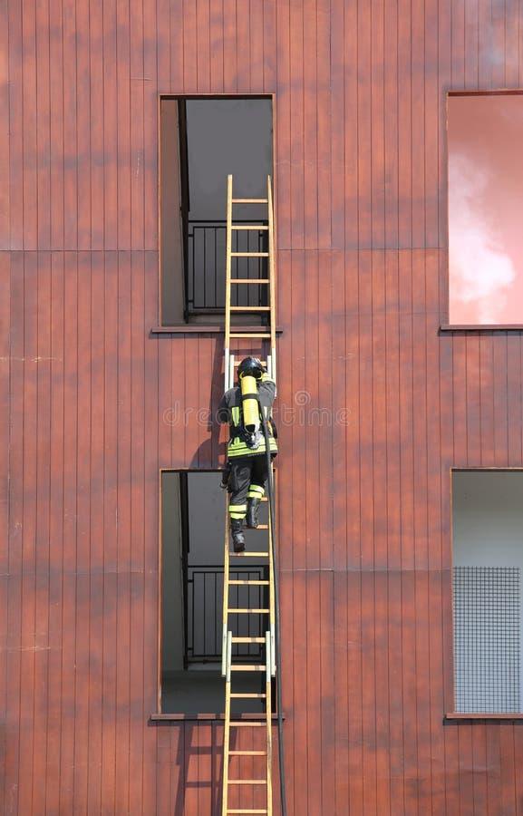 pompiere sulla scala con la maschera ed il cilindro di ossigeno fotografie stock