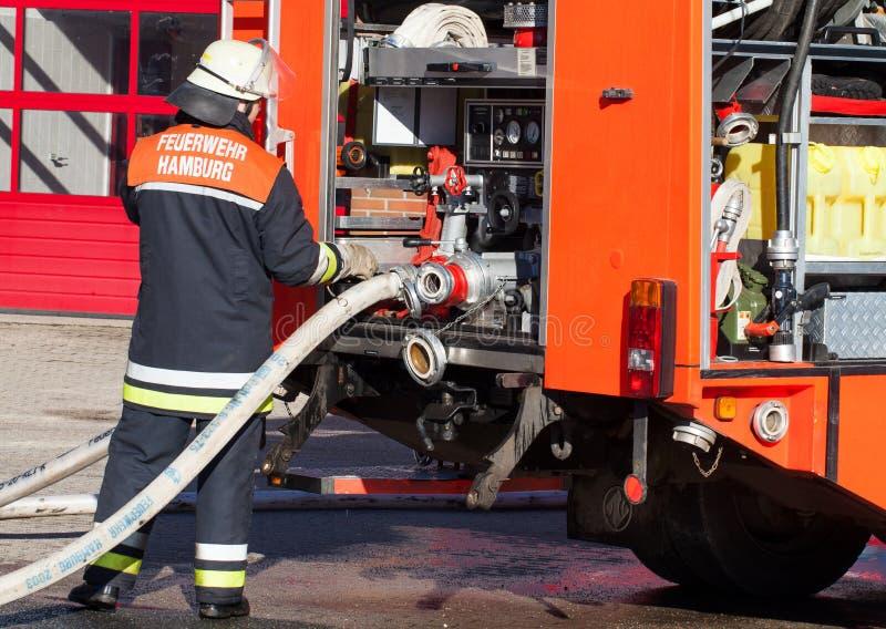 Pompiere tedesco del corpo dei vigili del fuoco sul camion dei vigili del fuoco 2 immagini stock