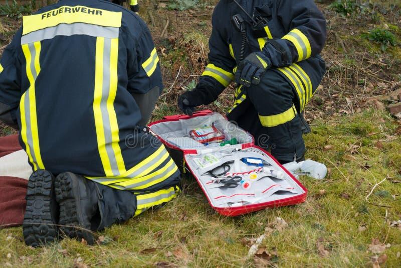 Pompiere in uso con la cassetta di pronto soccorso - pompiere di Serie fotografie stock