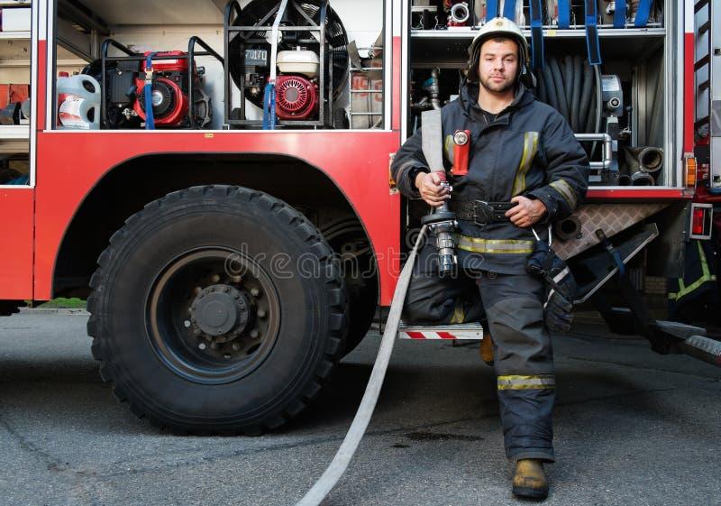 Pompiere vicino al camion con attrezzatura fotografie stock
