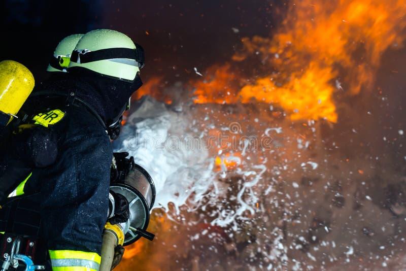 Pompiere - vigili del fuoco che estinguono una grande fiammata fotografia stock libera da diritti